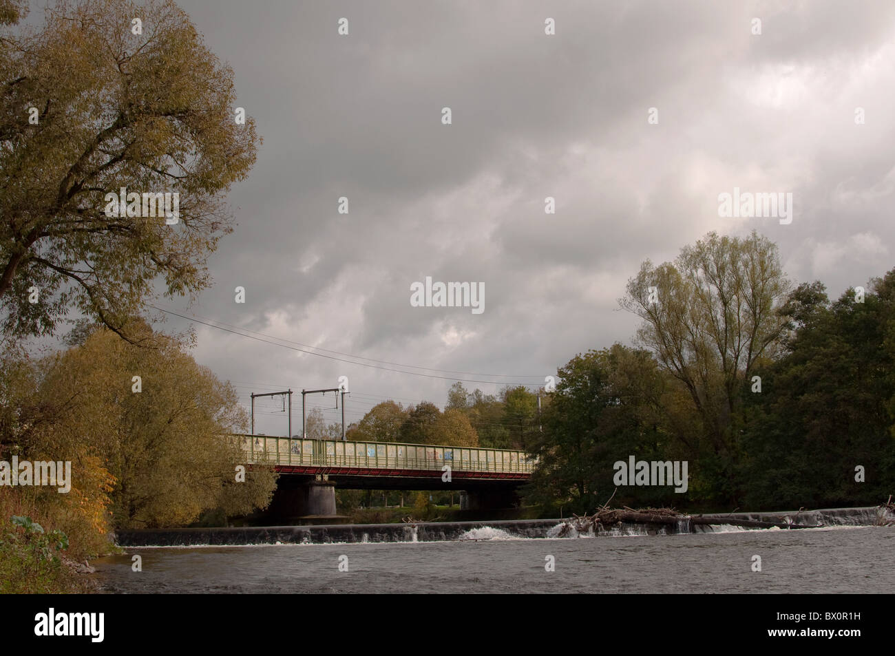 The river Ourthe under a railway bridge in the countryside under a very cloudy sky. By Pierre Jacques DESPA. - Stock Image