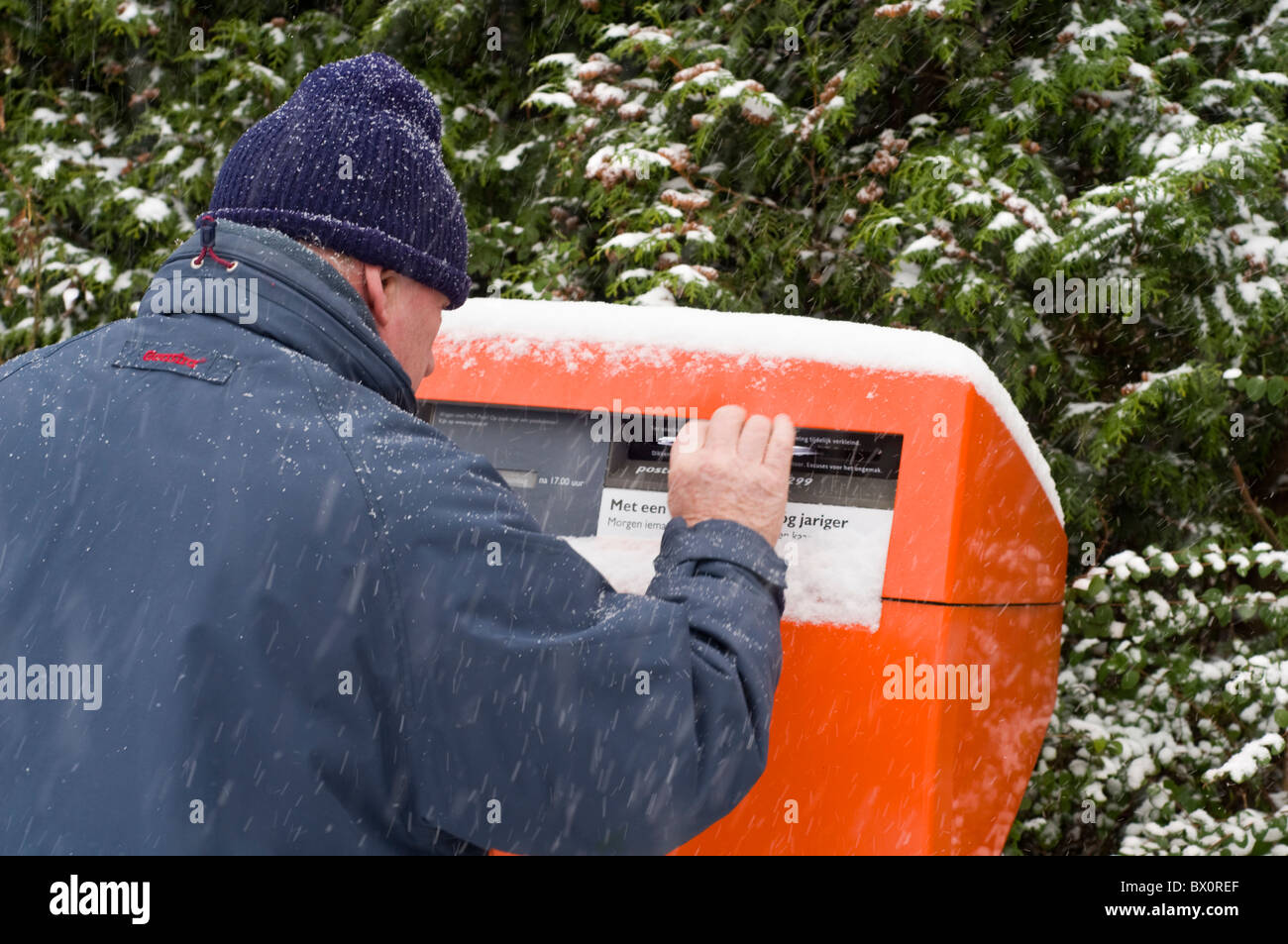 A man posting a letter during a snow shower in the Netherlands Stock Photo