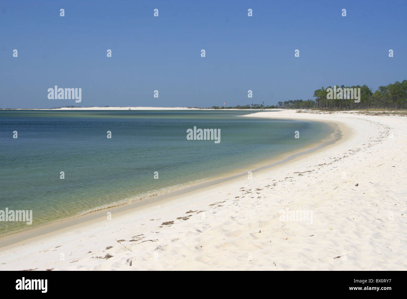 strand of sugar white sand and aqua water on NAS Pensacola Navy base blue sky - Stock Image