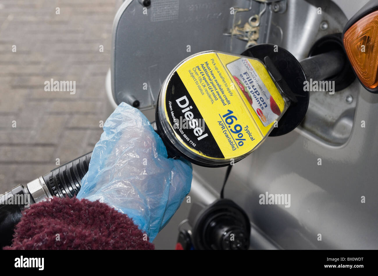 Motorist wearing plastic disposable gloves whilst holding a fuel pump to fill a vehicle with Diesel at a gas filling - Stock Image