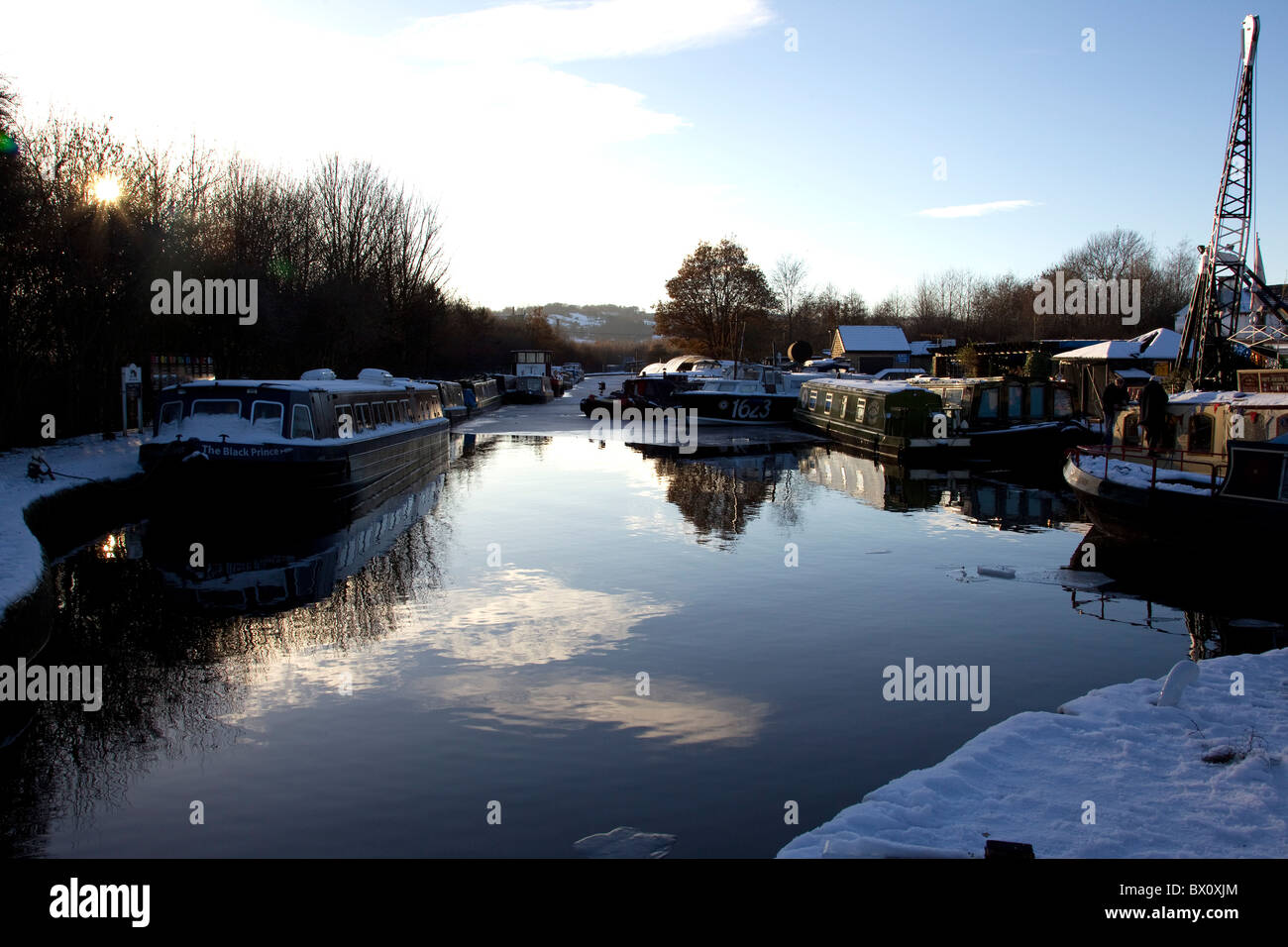 View of narrow boats moored at the Shepley Bridge Marina in Yorkshire in bitter wintery conditions - Stock Image