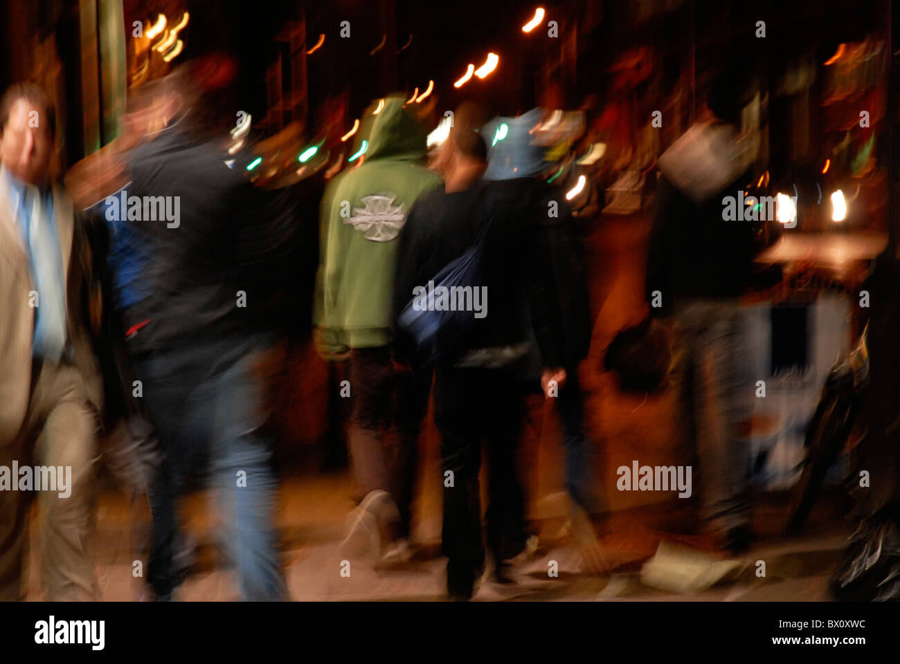 Urban gang of youth in city streets at night - Stock Image