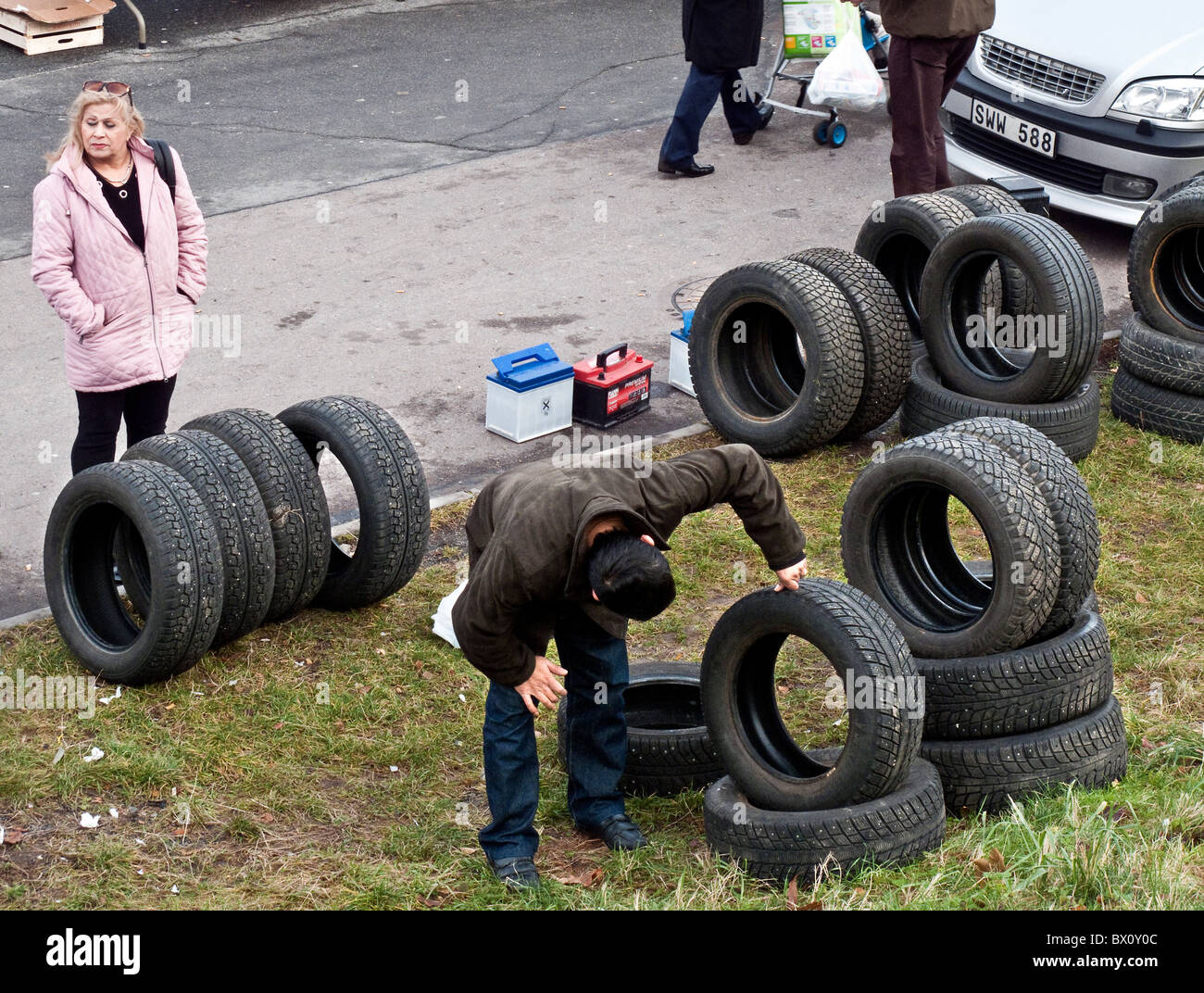 A man carefully examines second hand tires displayed at crowded weekend flea market in outskirt of Gothenburg, Sweden. - Stock Image