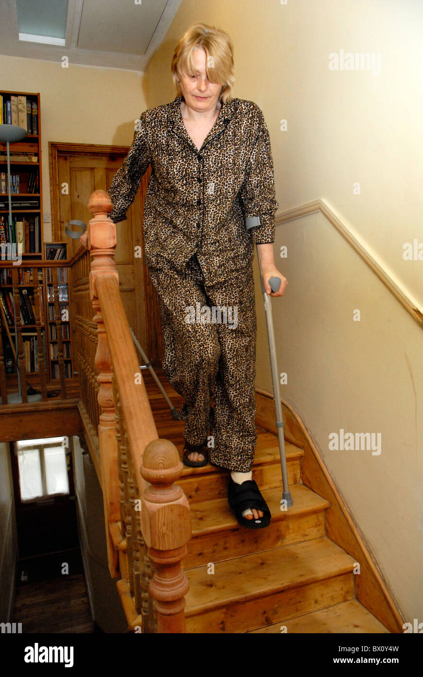 Woman Walking Down Flight Of Stairs On Crutches Following An Stock