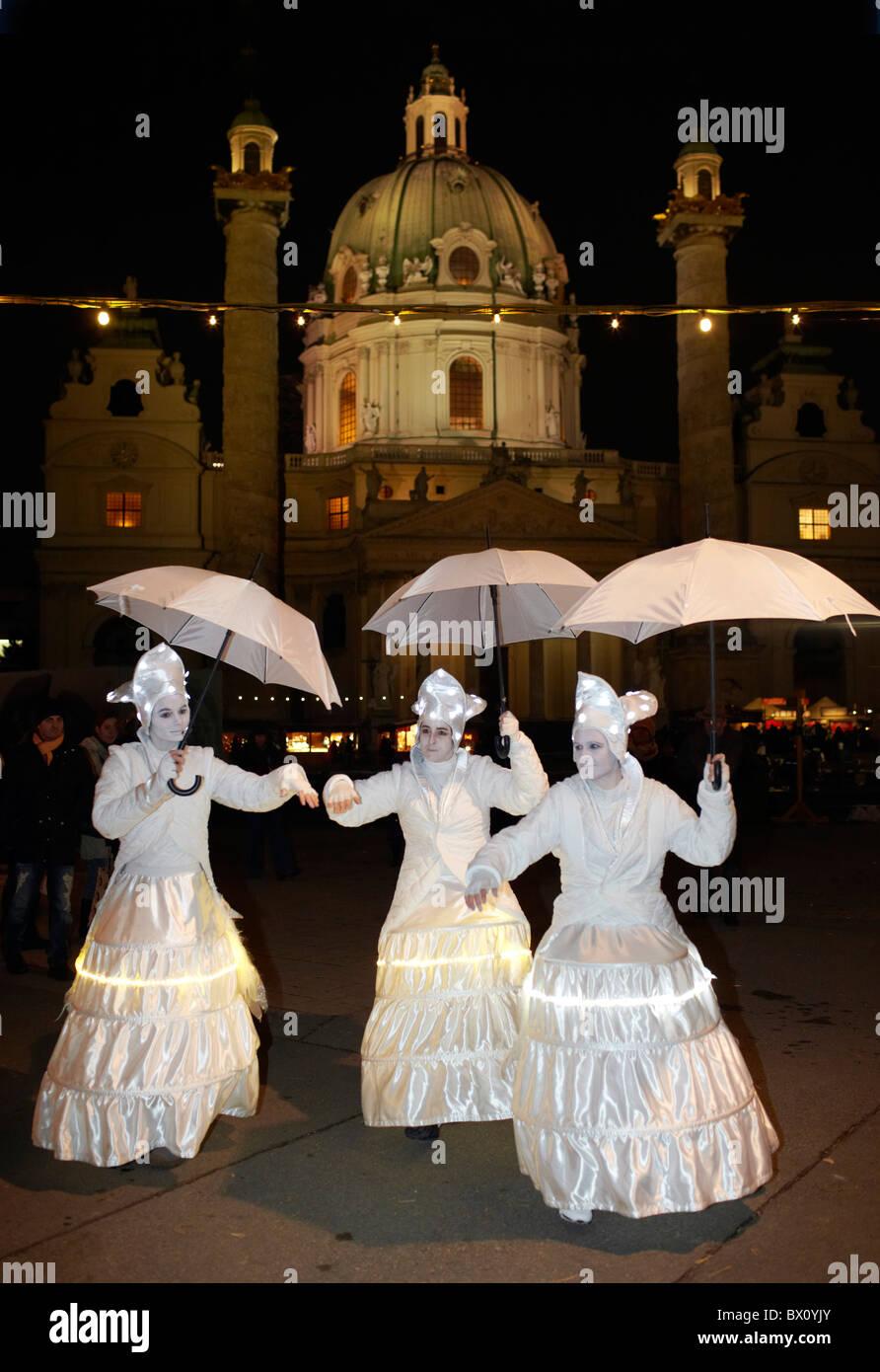3 women dressed in white outfit Karlsplatz Christmas market - Stock Image