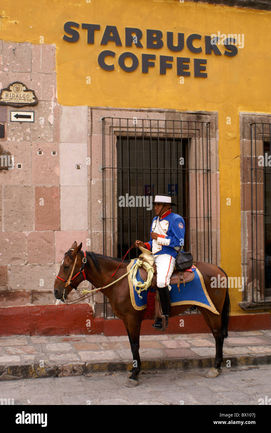 Spanish policeman in traditionlal costume on horseback outside Starbucks Coffee shop in San Miguel de Allende, gentrification,americanization - Stock Image