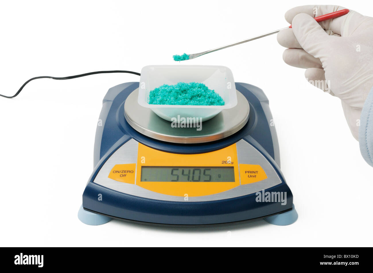 Measuring the mass of a chemical (Cupric Chloride dihydrate crystals) with electronic balance - Stock Image