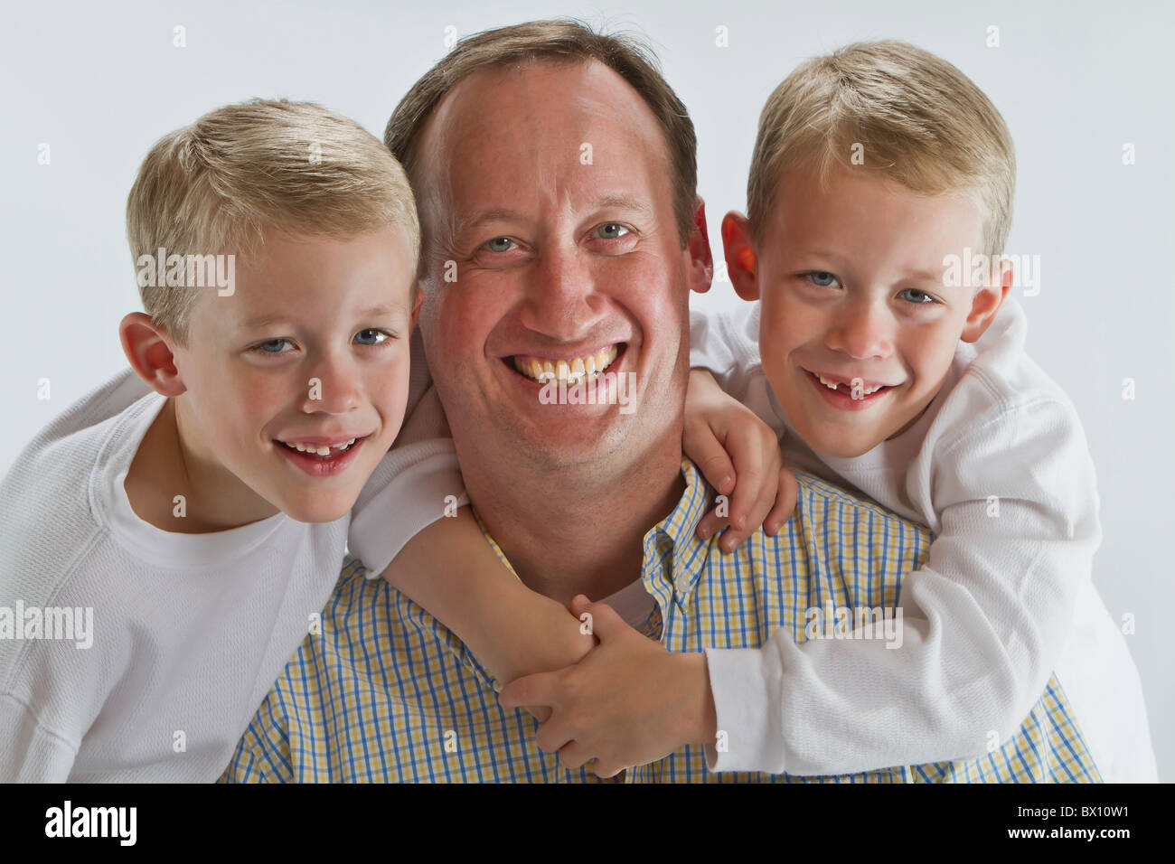 Happy father with 6 years old identical twins smiling - Stock Image