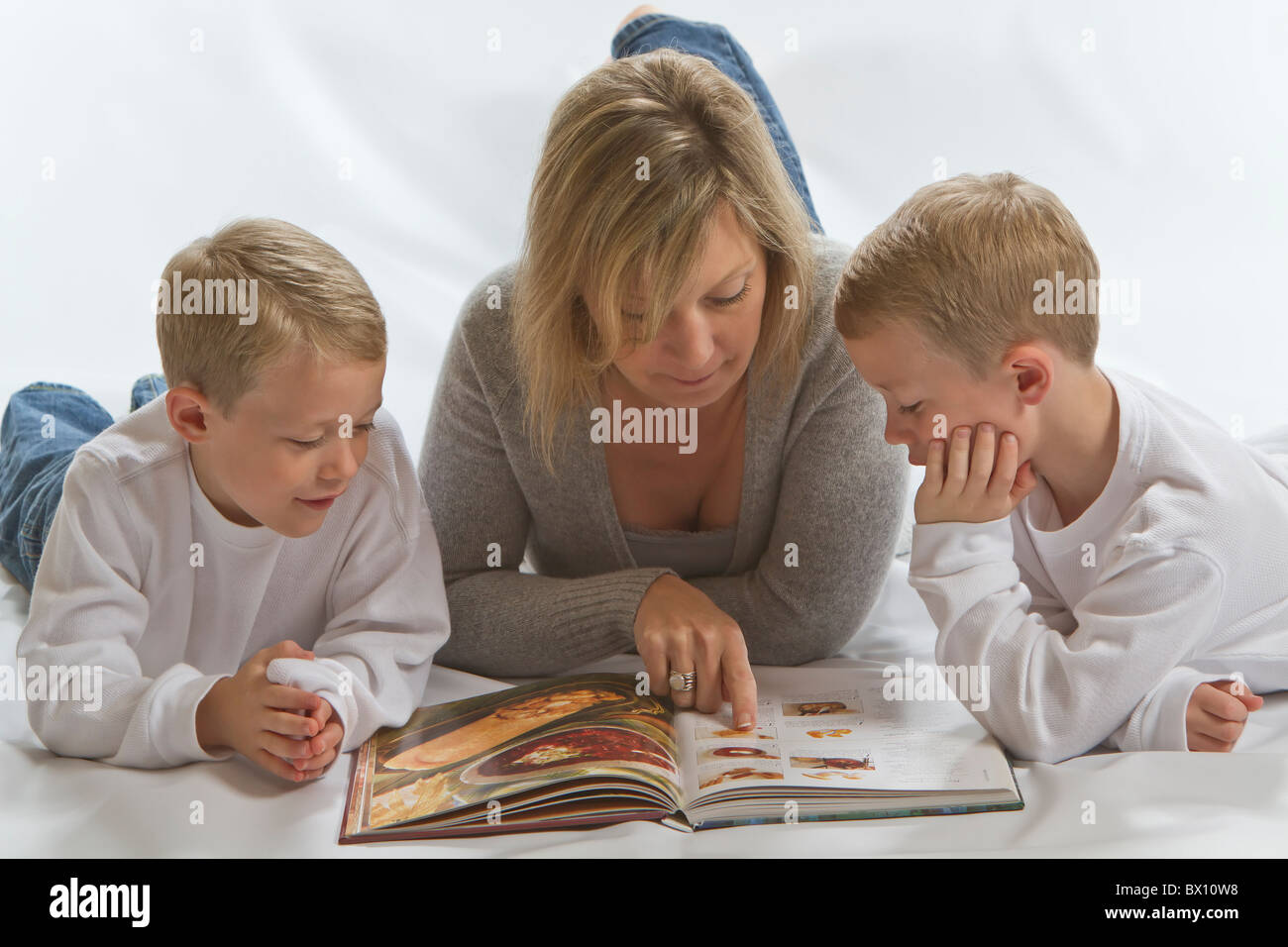 Identical twin boys doing homework with their Mom - Stock Image