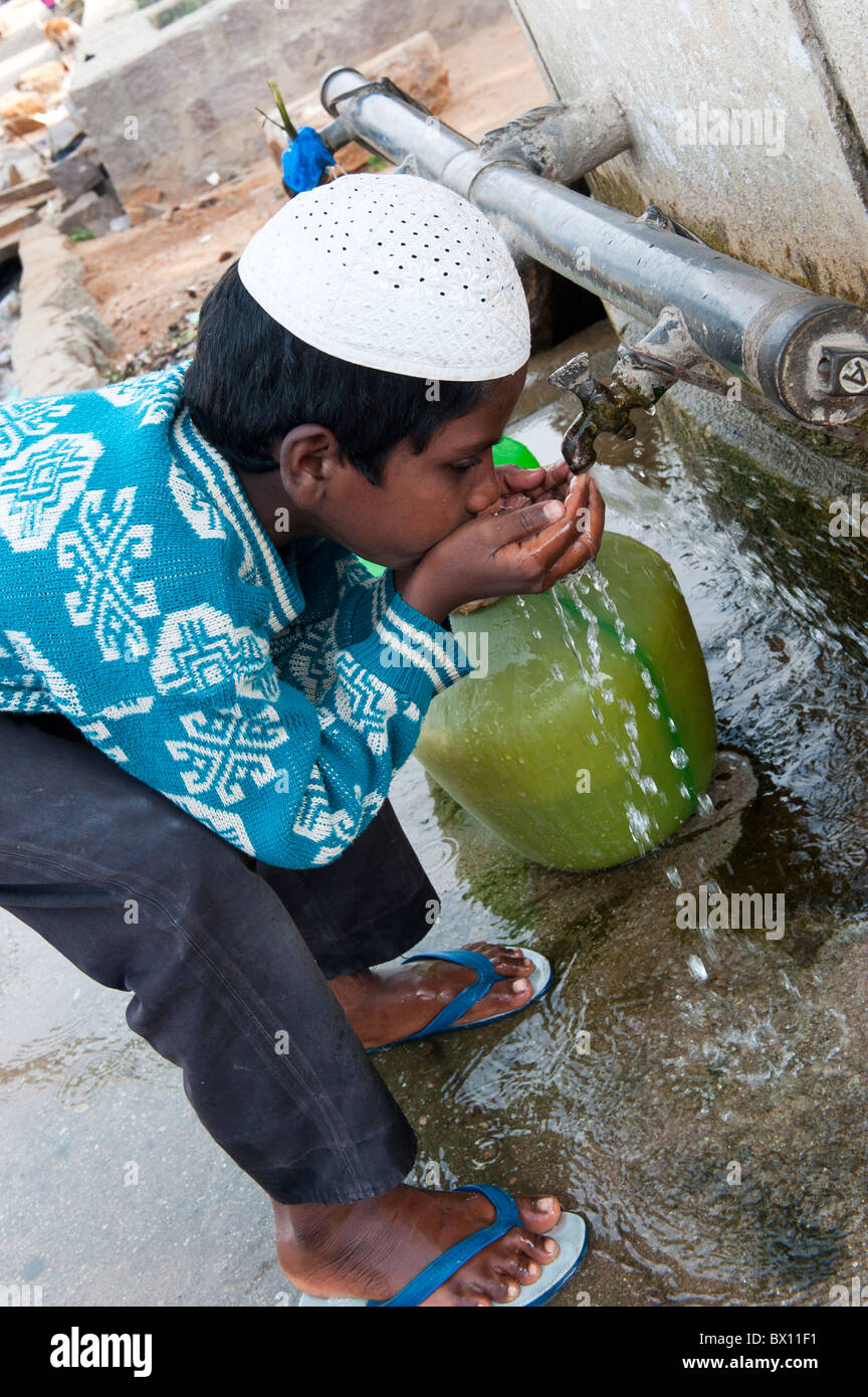 Indian Muslim Boy Drinking Water From A Tap Outside A House In Bukkapatnam,  Andhra Pradesh, India