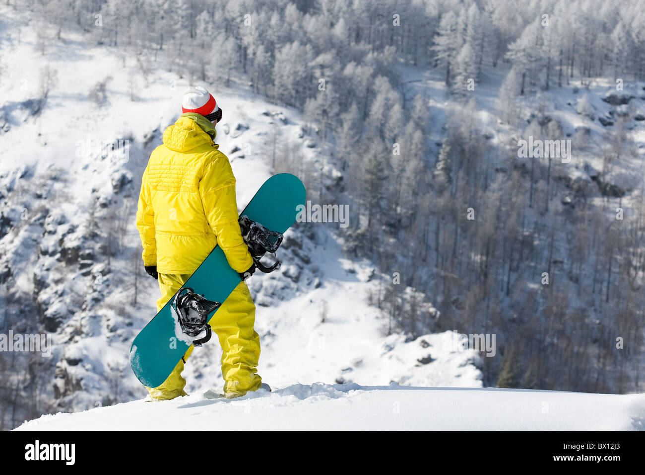 Rear view of snowboarder standing in snowdrift in winter - Stock Image