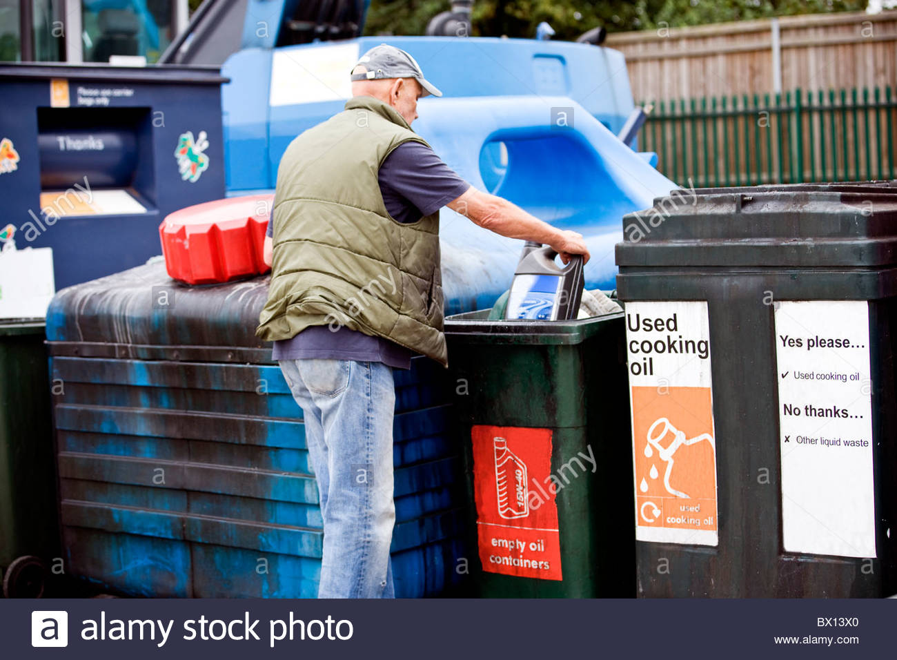 A senior man recycling an empty oil container - Stock Image