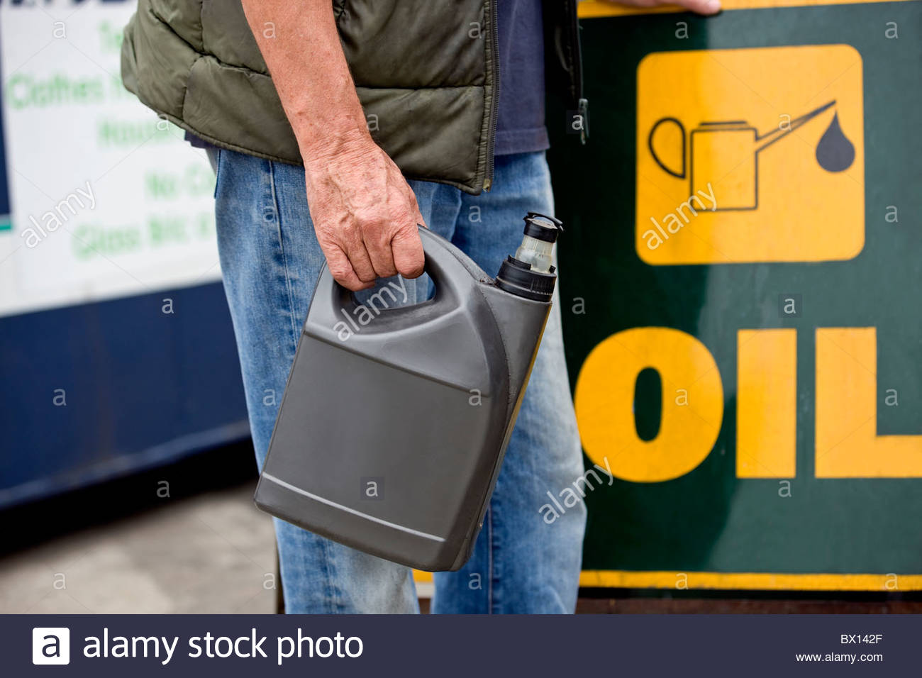 A senior man holding an oil container in a recycling center, close-up - Stock Image