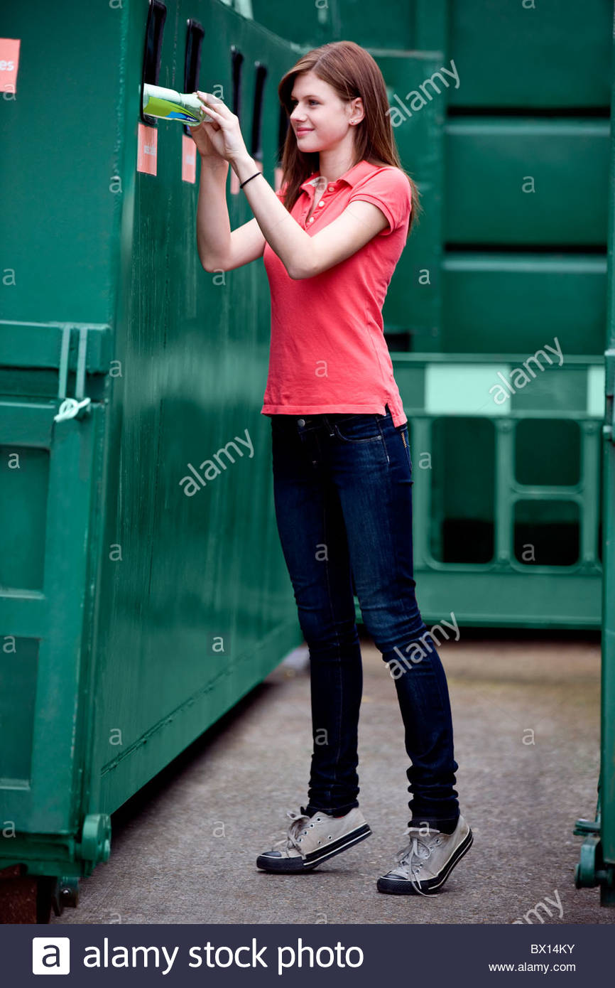 A teenage girl recycling a plastic bottle - Stock Image