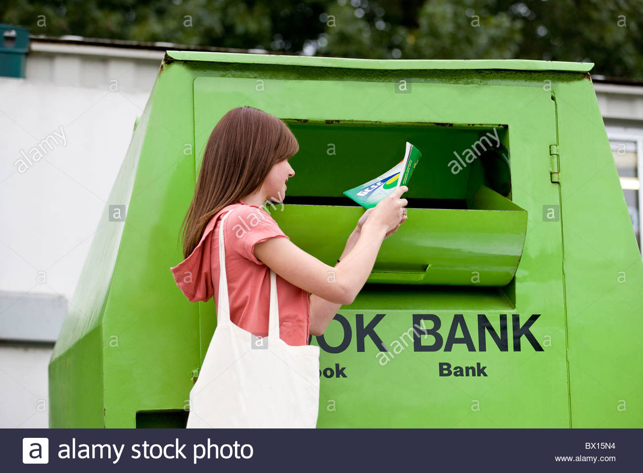A teenage girl recycling a school textbook - Stock Image