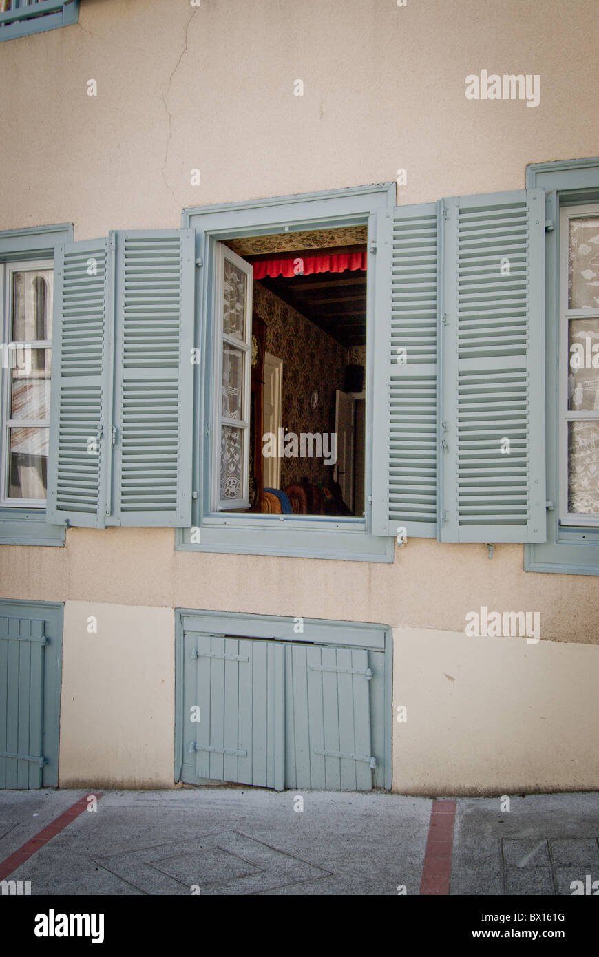 Pyreneeian house on steep street with Louvre shuttered windows - Stock Image
