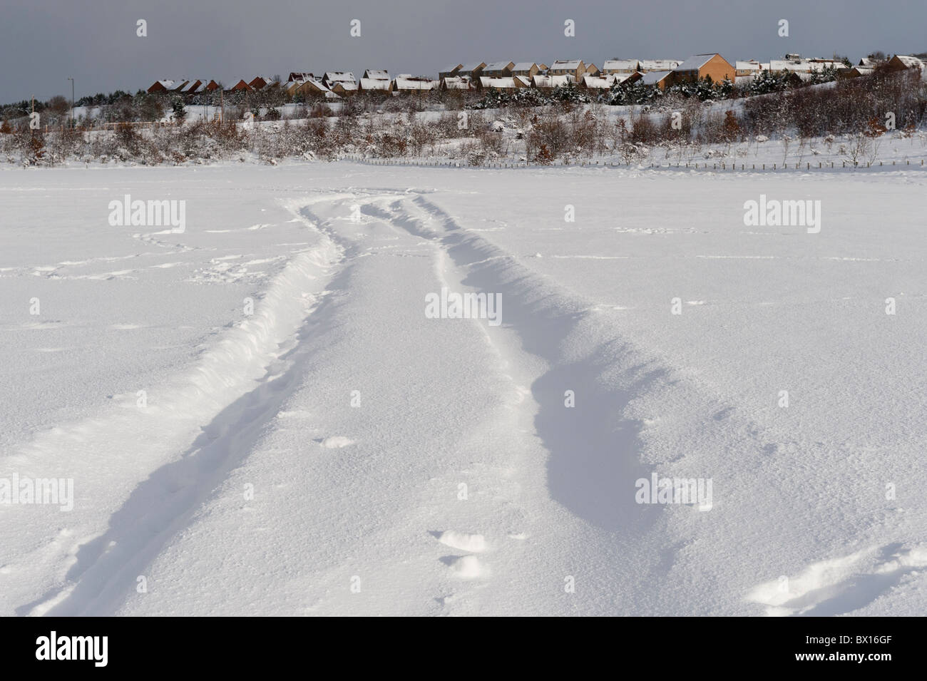 Tracks across a snow covered field. - Stock Image