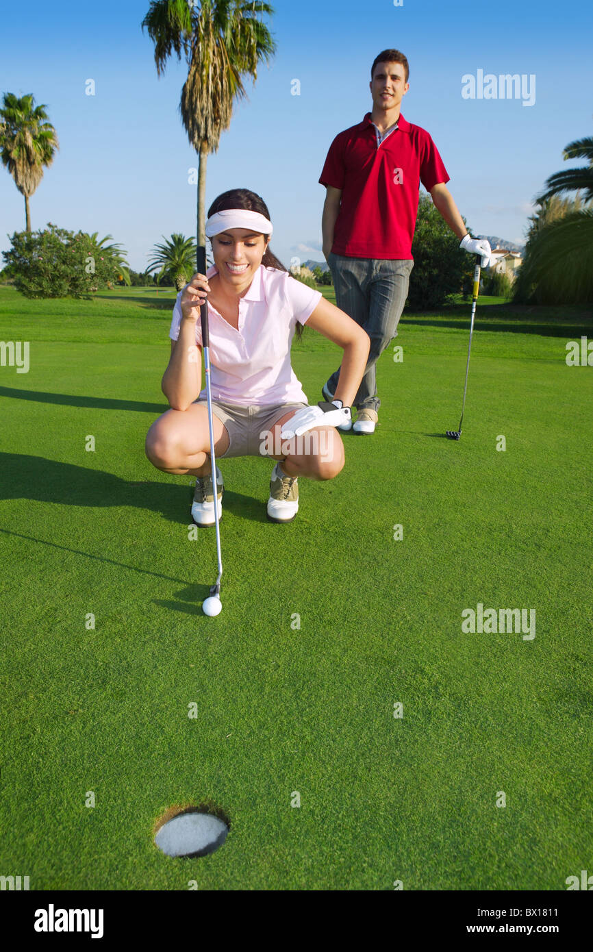 playing golf young woman looking and aiming for the hole - Stock Image