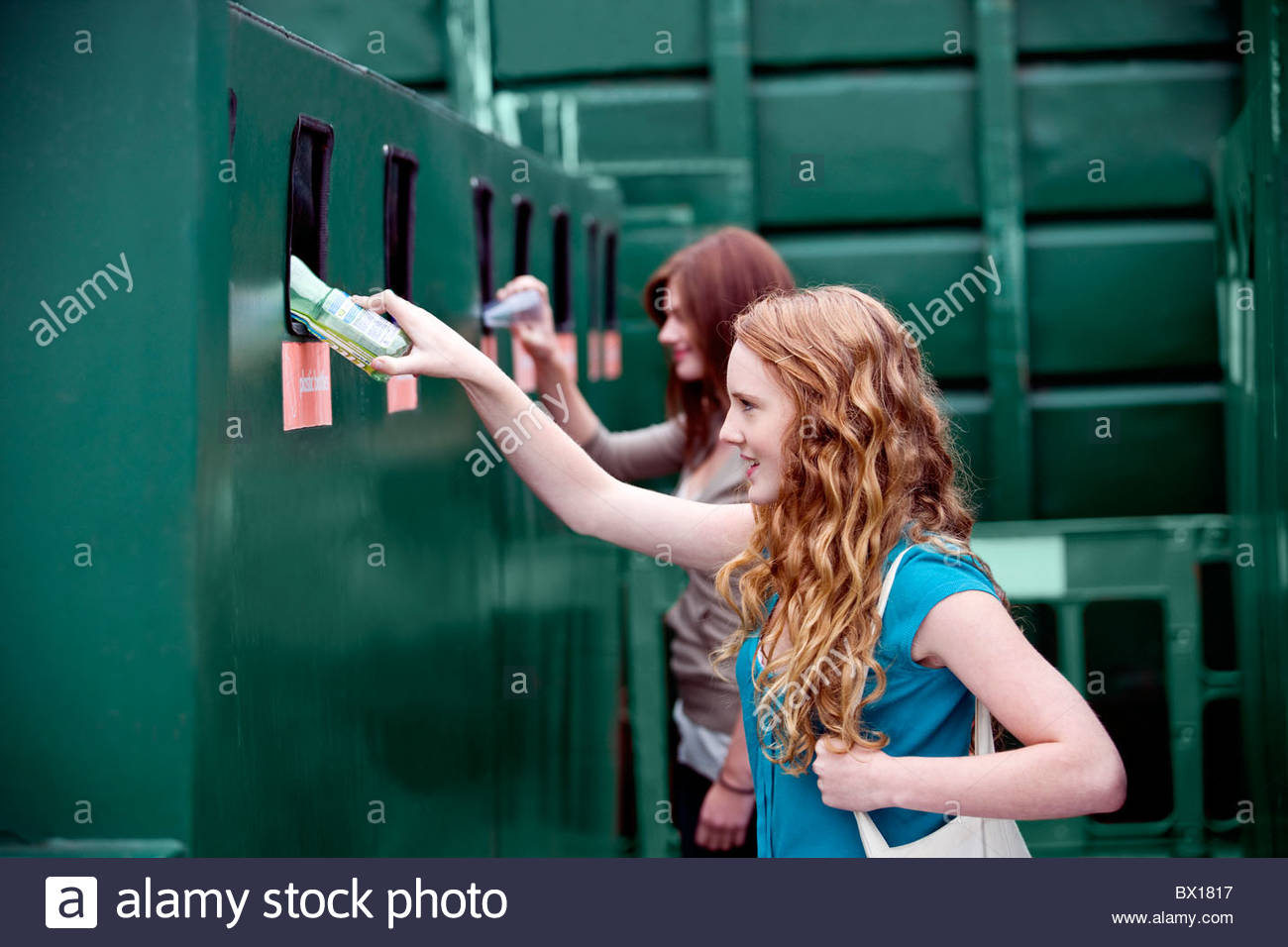 Two teenage girls recycling plastic bottles Stock Photo