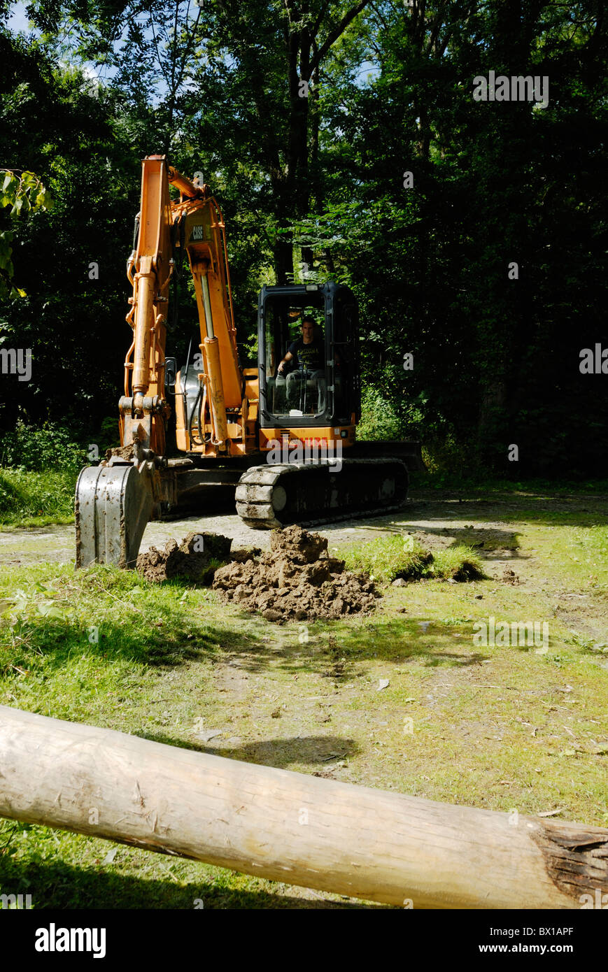 Tracked excavating machine digging a hole for a gatepost in woodland, Wales. - Stock Image