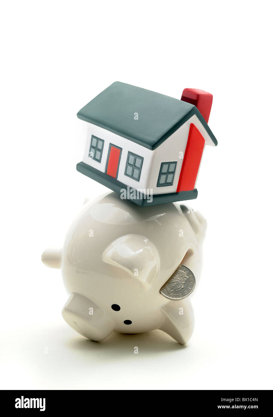 PIGGY BANK BALANCING HOUSE ON BACK RE HOUSEHOLD BUDGETS SAVINGS HOME OWNERSHIP CASH WAGES MORTGAGES RENTS ETC UK Stock Photo