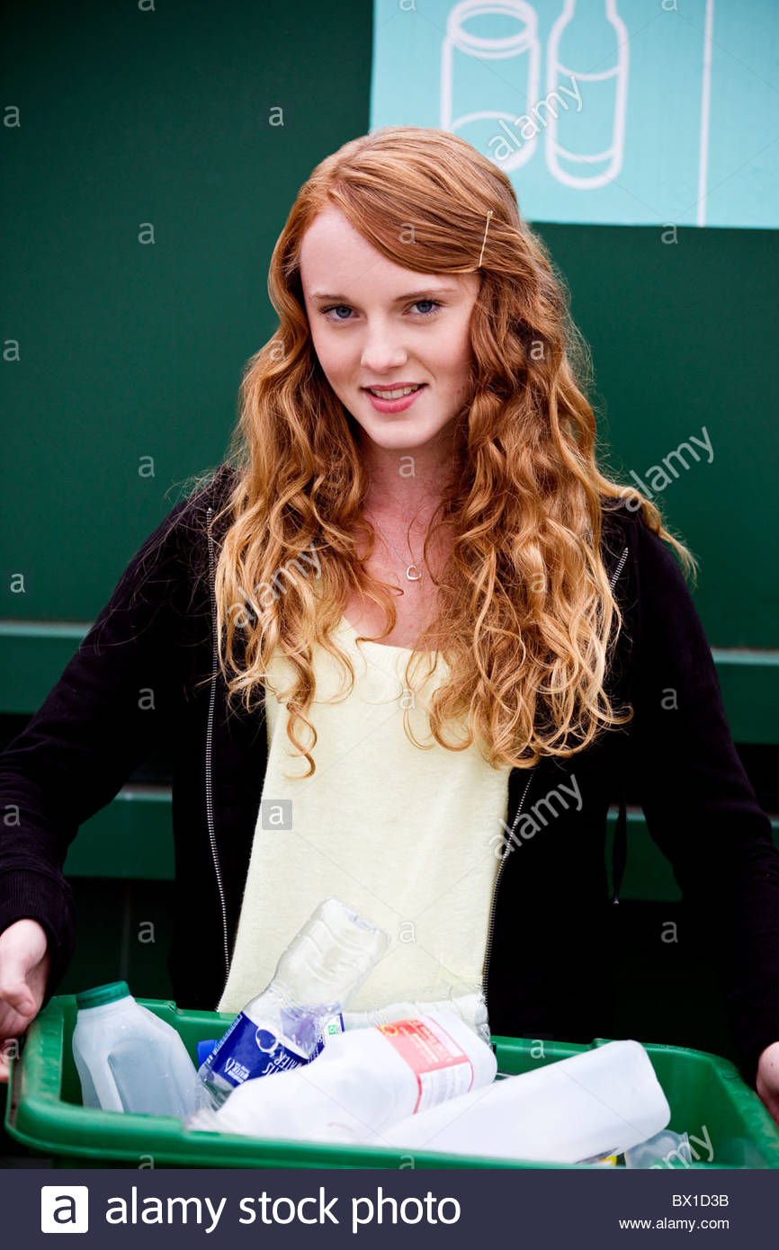 A teenage girl holding a recycling container - Stock Image