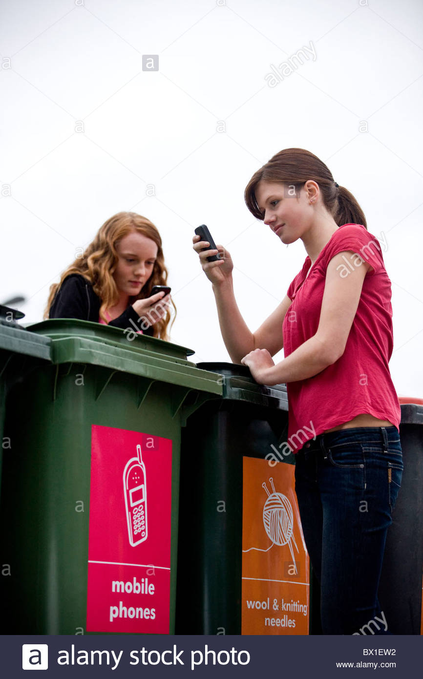 Two teenage girls using their mobile phones in a recycling center - Stock Image