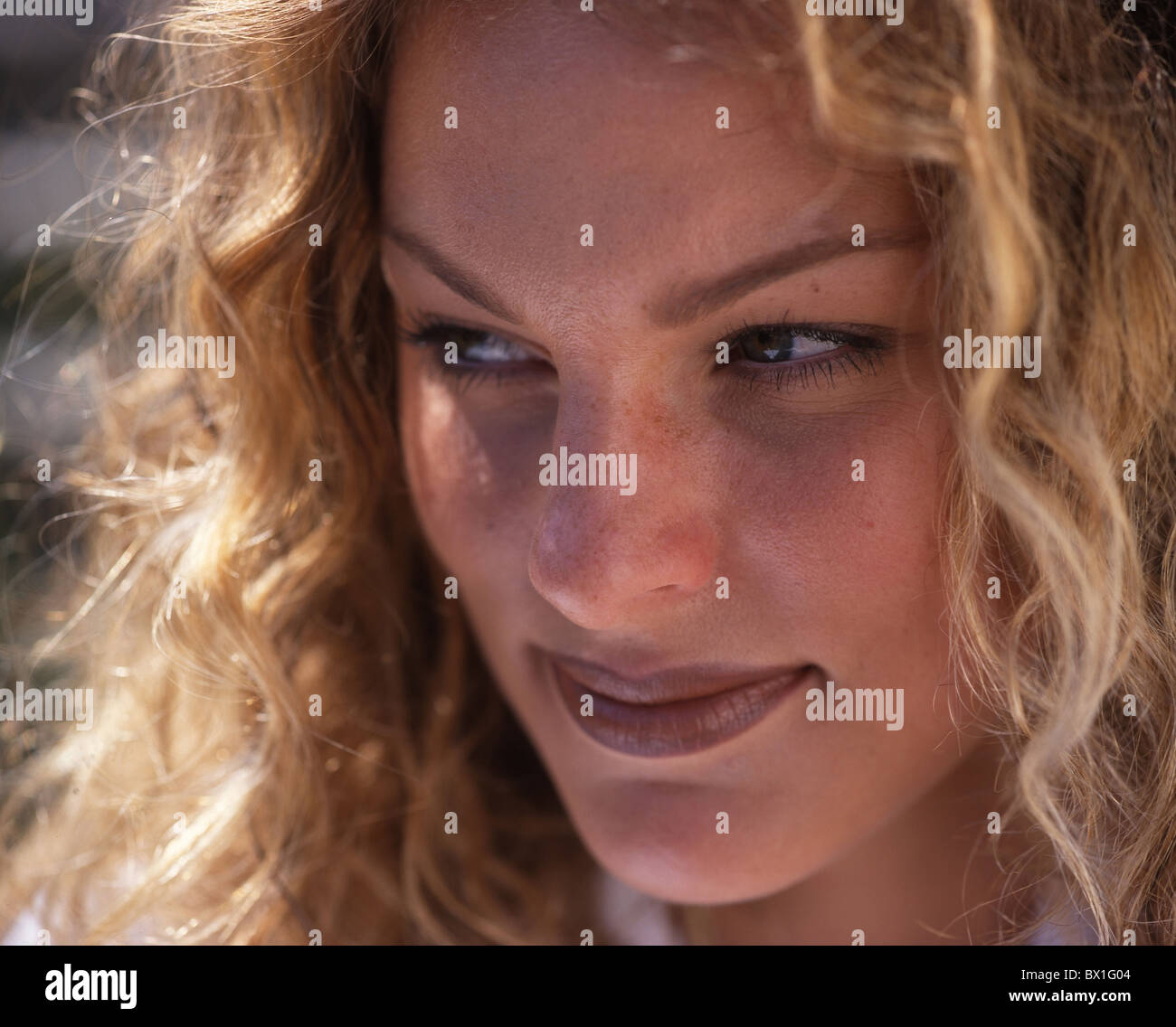 Woman face outside blond long hair locks portraits - Stock Image