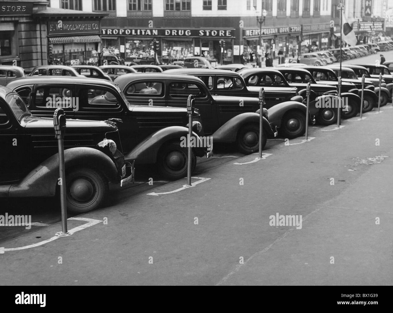 Vintage photo taken in 1938 of a row of cars parked diagonally in front of a series of parking meters in Omaha, - Stock Image