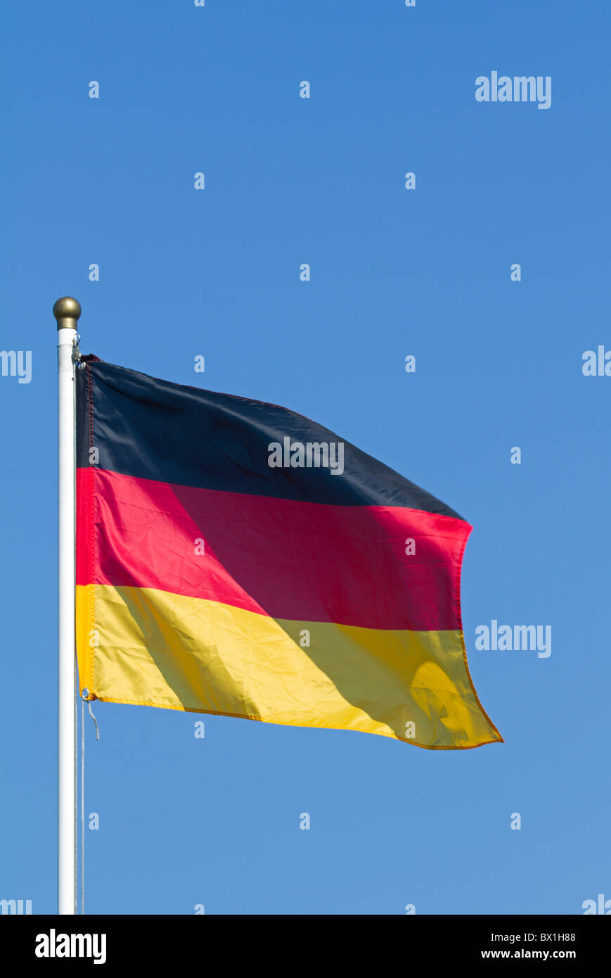Breezing Germany flag with blue sky - Stock Image