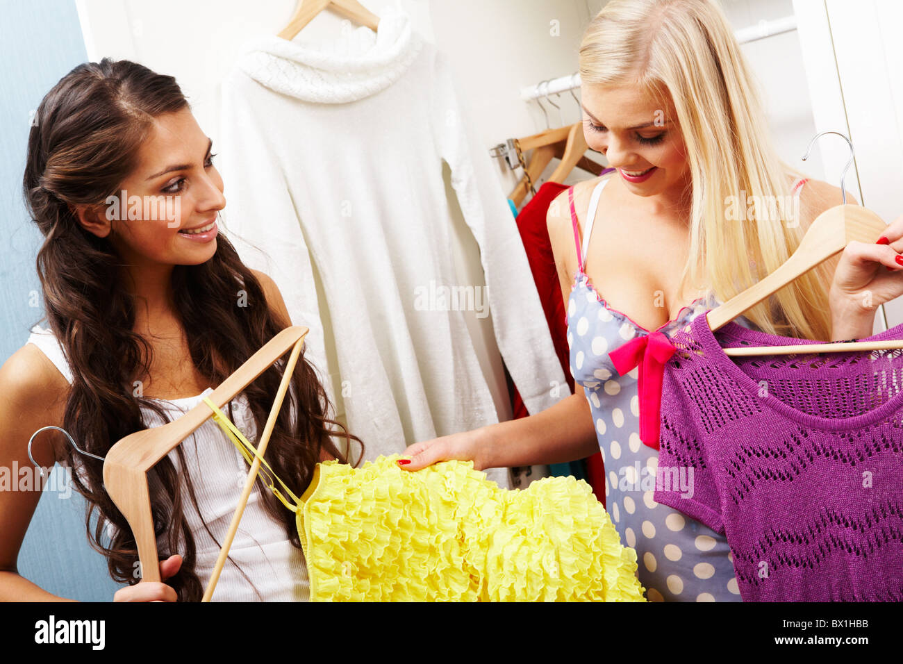 Image of pretty females looking at smart dress while choosing a right one - Stock Image