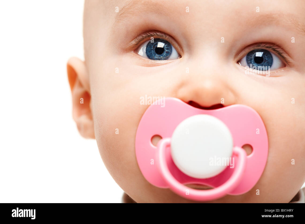 Face of adorable baby with pacifier in mouth looking at camera Stock Photo