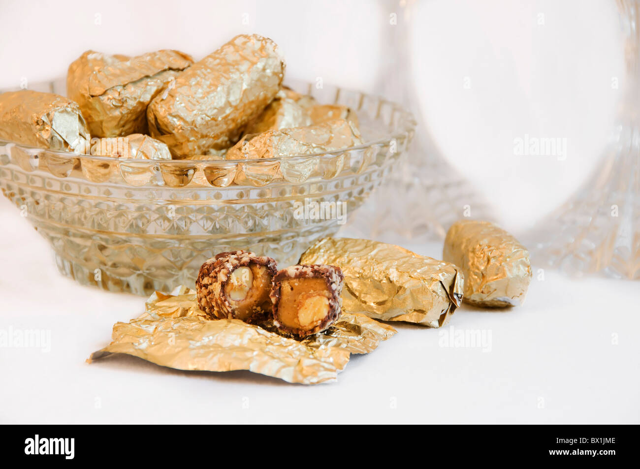 Gold foil wrapped pieces of Almond Roca candy are placed in a crystal bowl with an unwrapped candy in front. - Stock Image