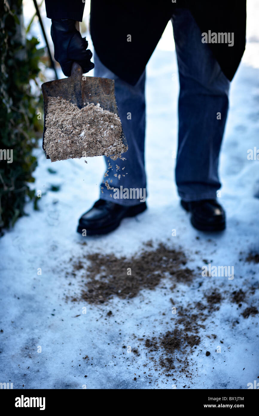 Older person using grit on an icy path - Stock Image
