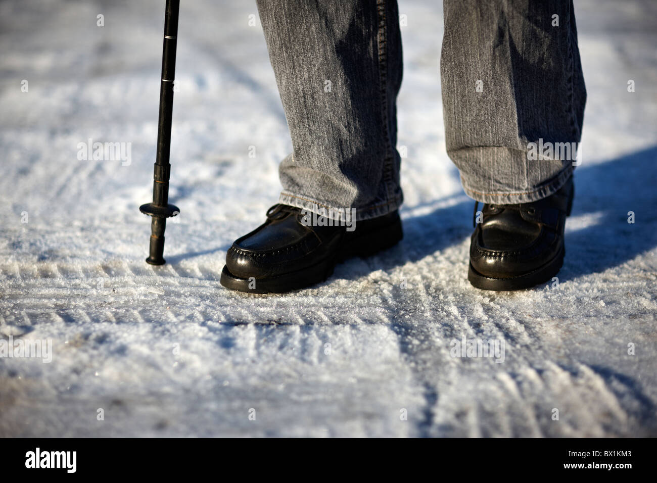 Older person walking on an icy pavement with stick - Stock Image