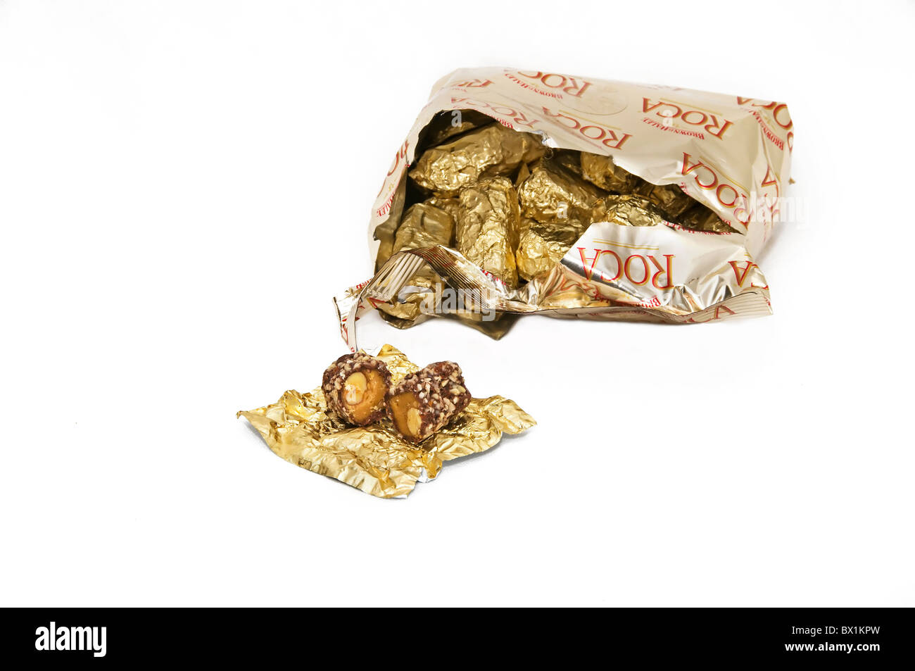An open piece of Almond Roca candy sits in front of an open bag filled with gold foil wrapped pieces. - Stock Image