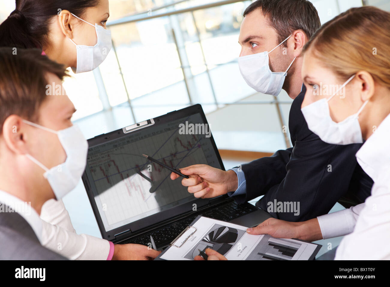 serious-business-partners-in-protective-mask-looking-at-screen-of-BX1T0Y.jpg