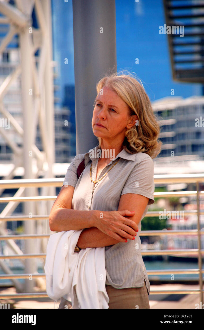 Woman middle age old person outside standing leave Sad lonely thoughtful problematical worries problem - Stock Image