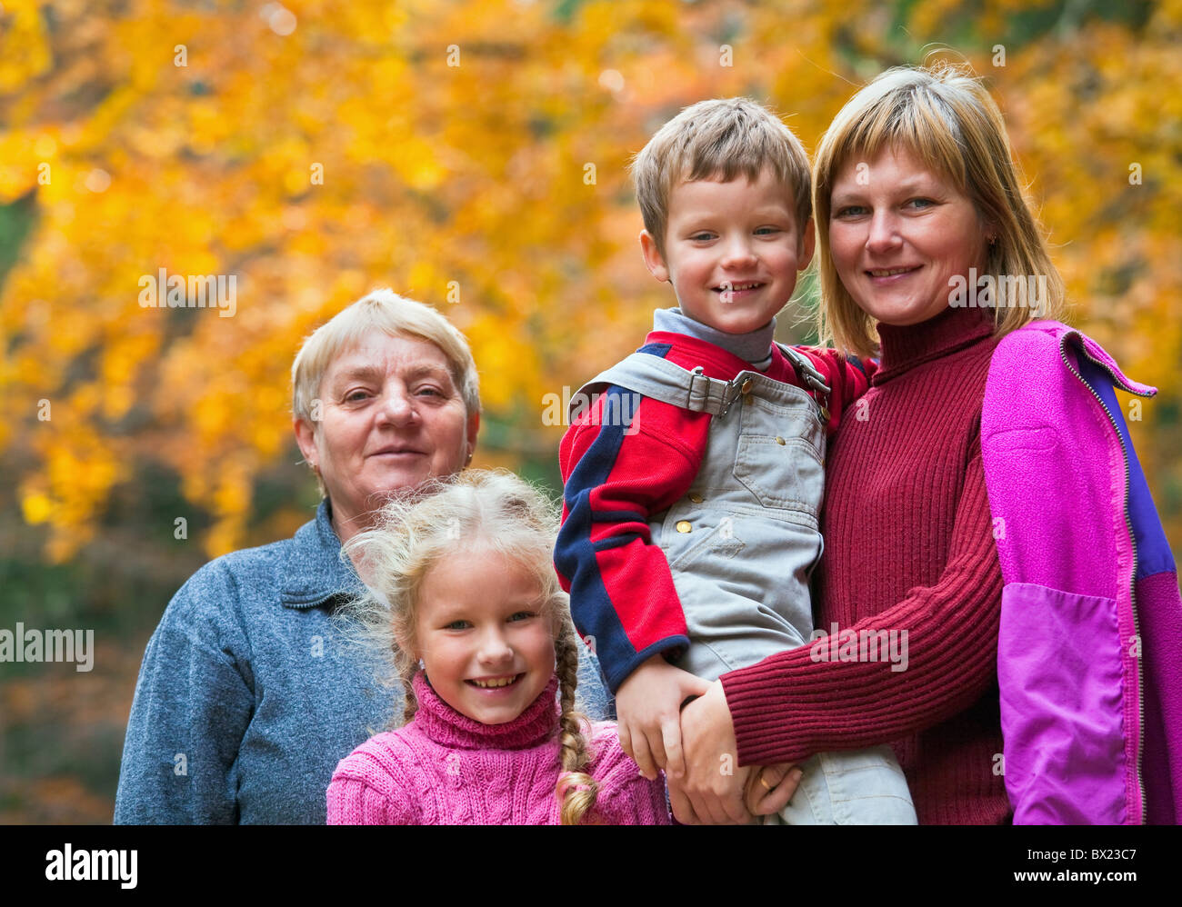 Happy family outdoor portrait in a autumn mountain walk - Stock Image