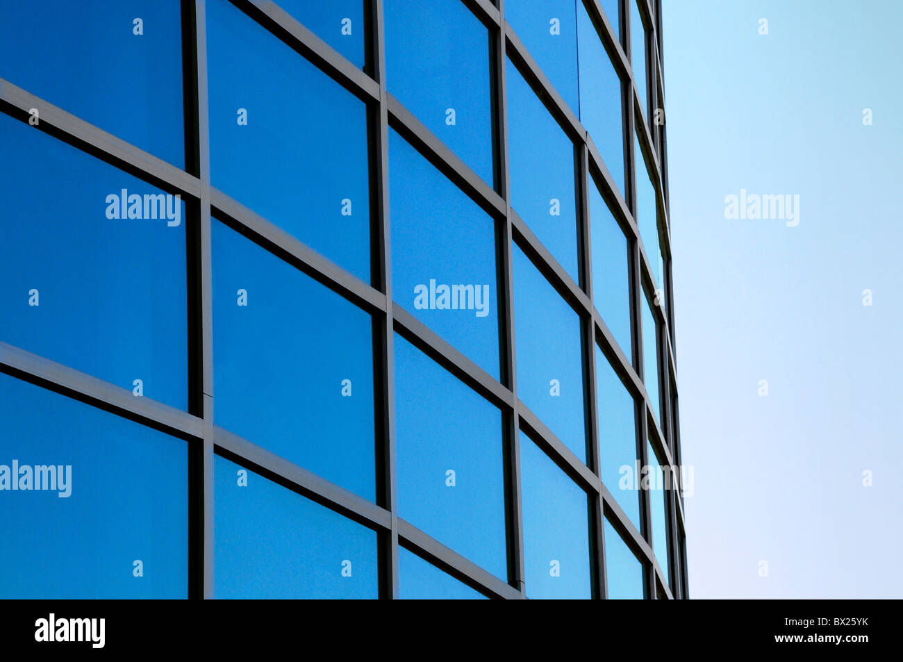Curved exterior windows of a commercial office building reflecting a blue sky - Stock Image