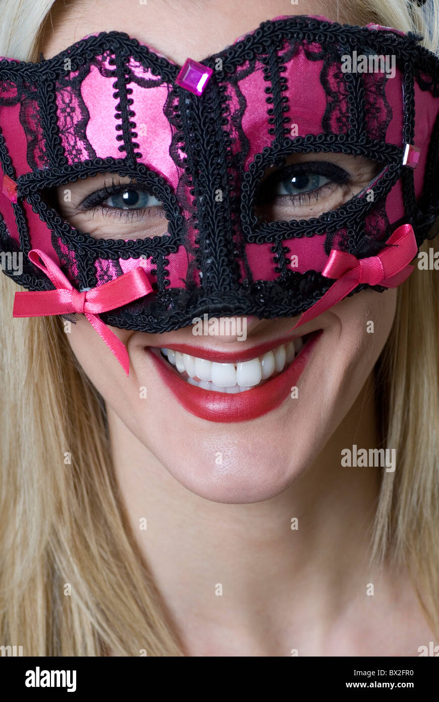 Young woman in pink party mask - Stock Image