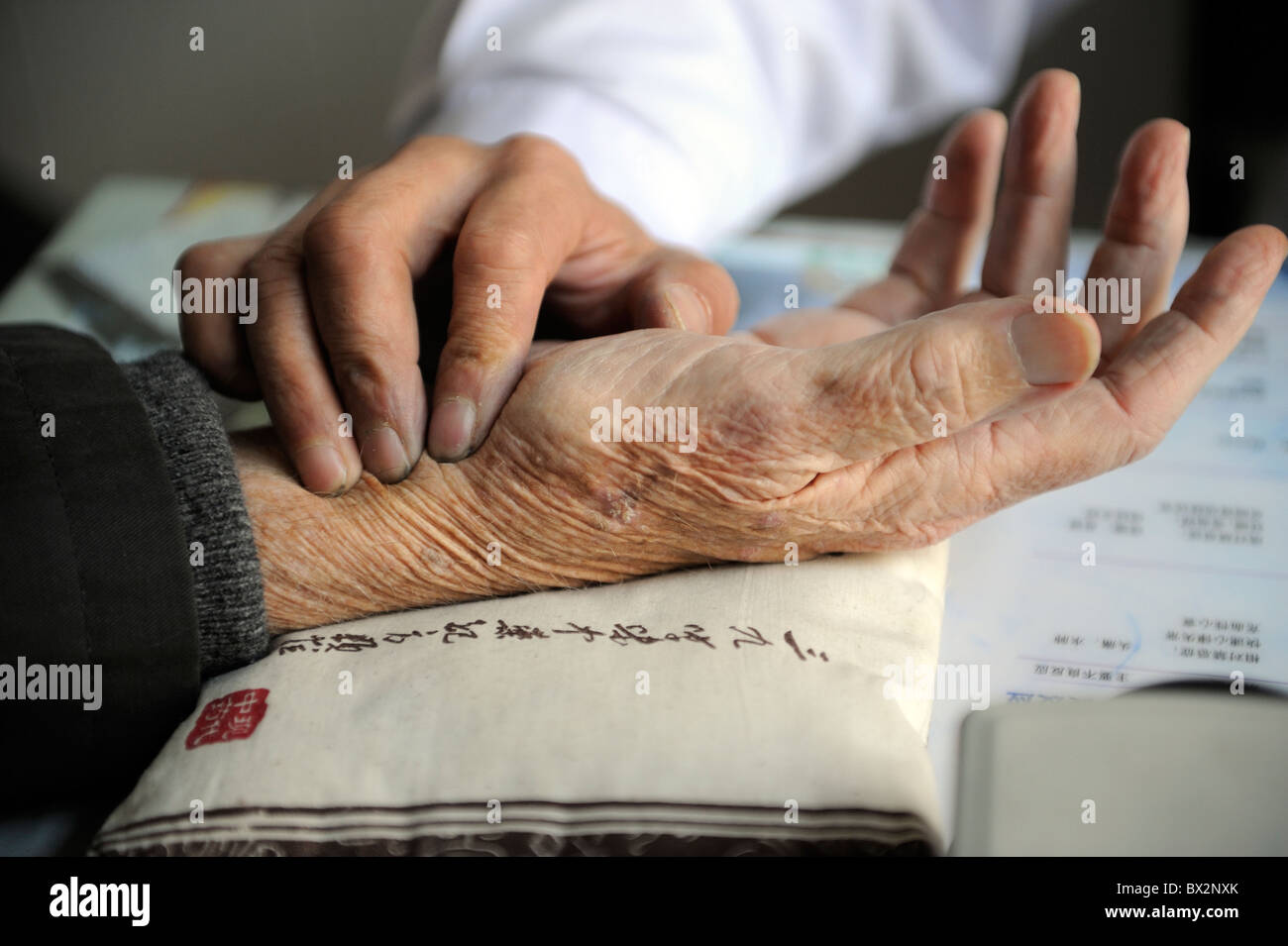 Doctor of traditional Chinese medicine checking an old man's pulse in a hospital in Beijing, China. 2010 - Stock Image