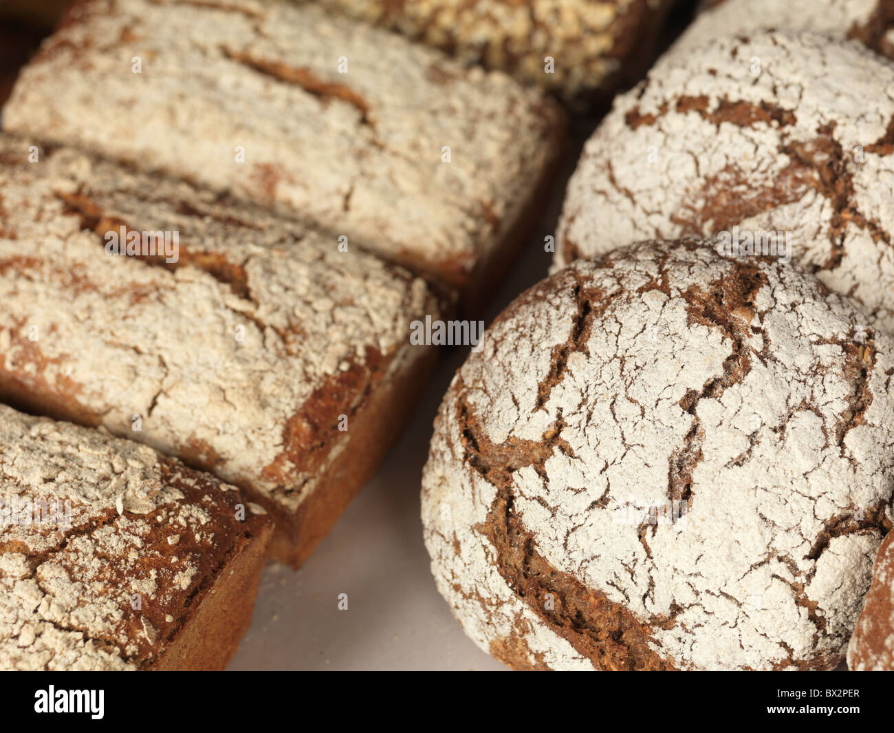 Freshly baked bread topped with flour on a tray - Stock Image