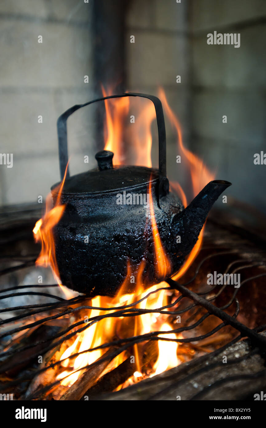 A soot-blackened tea pot sits on an open fire. - Stock Image