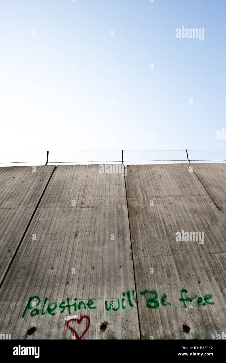 The graffiti slogan 'Palestine Will Be Free' is painted on the Israeli separation barrier's 8 meter - Stock Image