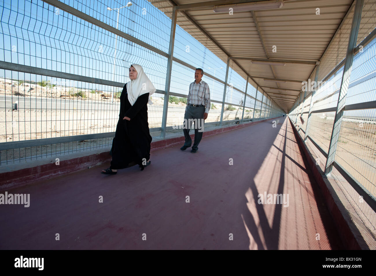 Palestinians walk through a caged terminal extending from the Erez crossing point from Israel to Gaza. - Stock Image