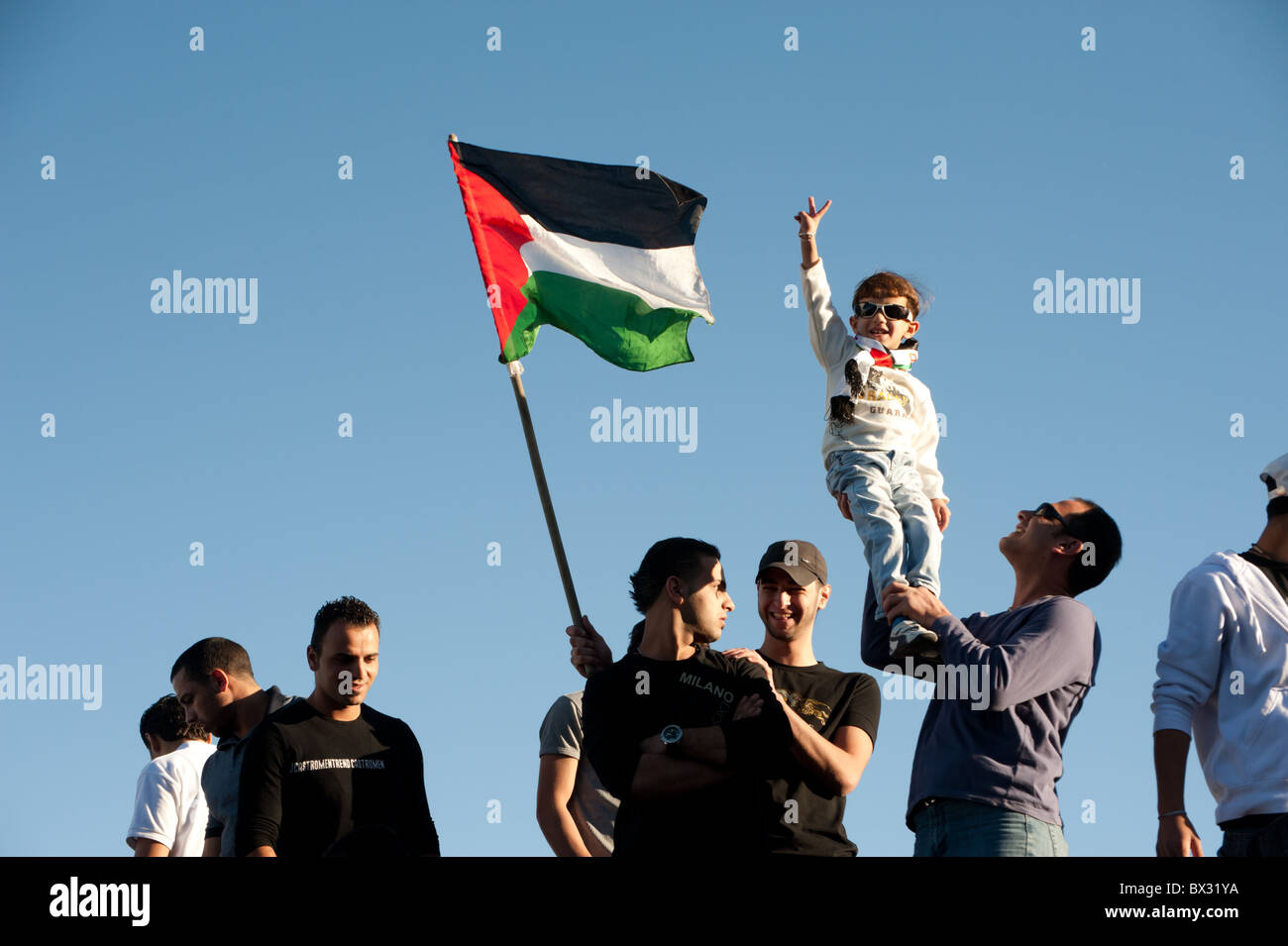 A Palestinian boy makes a peace sign as protesters fly the Palestinian flag at a rally against house demolitions - Stock Image