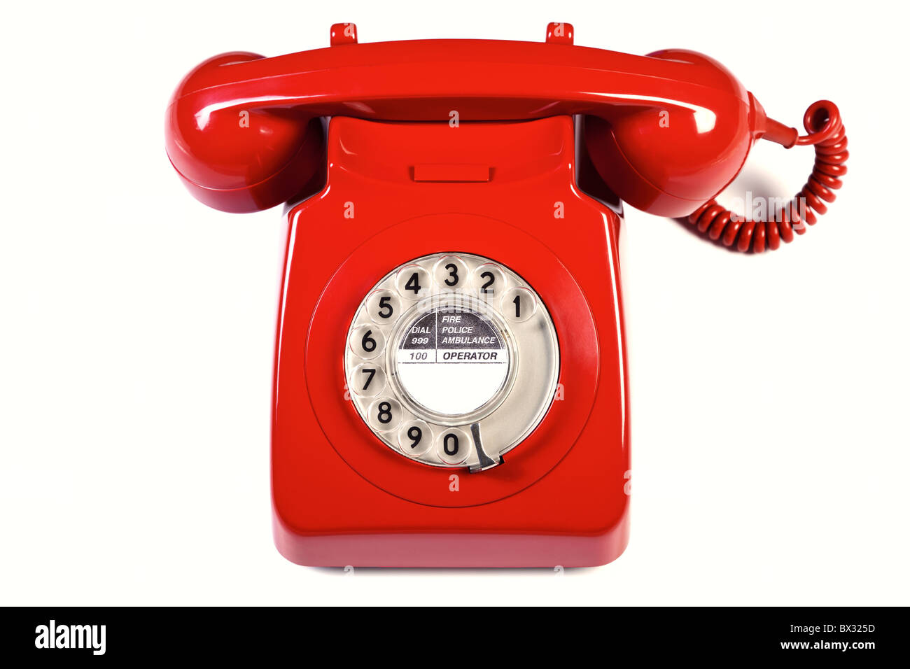 Photo of a retro red telephone isolated on a white background. - Stock Image