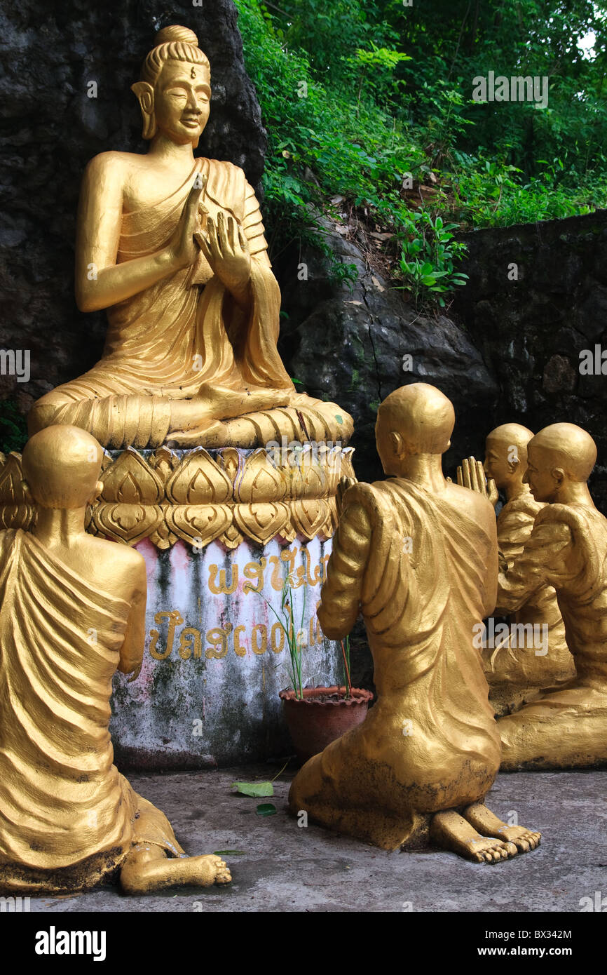 Gold sitting buddha surrounded by monk statues, Phou Si Hill, Luang Prabang, Laos, Asia - Stock Image