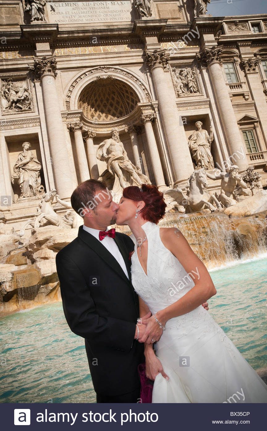 Newlyweds kissing in front of Fontana di Trevi - Stock Image